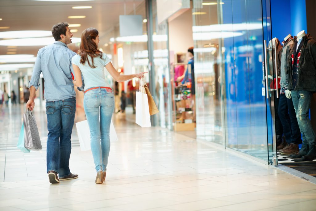 Shot of a happy young couple carrying shopping bags while walking through a mall